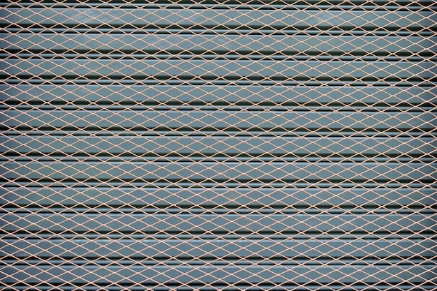 Wire mesh fence on a background of gray steel doors