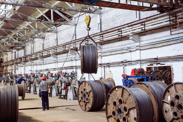 Wire rod, fittings in warehouses. worker alongside a bundle with catalkoy. industrial storehouse at the metallurgical plant.