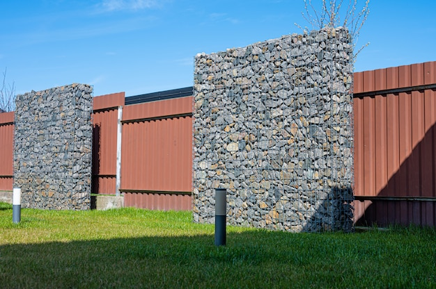 Wire and stone fence. decorative building made of stone gabion.
