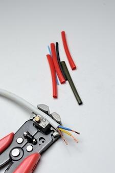 ワイヤーストリッパー、シールドされた3芯ワイヤー、白い背景の熱収縮チューブ。閉じる