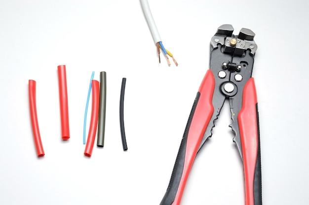 ワイヤーストリッパー、シールドされた3芯ワイヤー、白地に熱収縮チューブ。閉じる