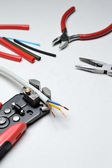 ワイヤーストリッパー、シールドされた3芯ワイヤー、白い背景のワイヤーカッター。閉じる