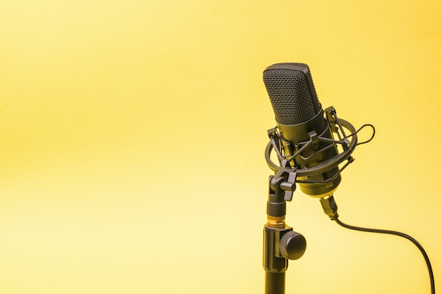 Wired condenser microphone on a stand on a yellow surface