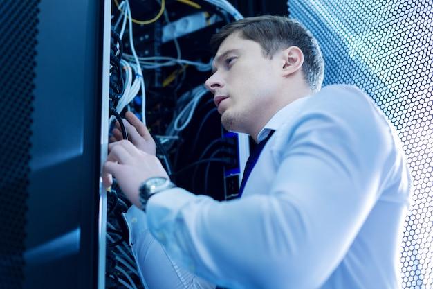 Проводное соединение. решительный опытный человек, работающий в сервисном шкафу и ремонтирующий провода