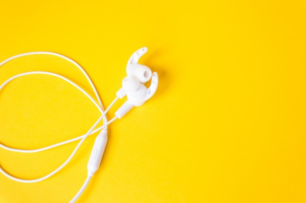 노란색 밝은 벽에 유선 된 헤드폰입니다. 공간 복사