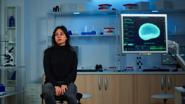 Проводной пациент ждет ученого-доктора в неврологической исследовательской лаборатории, посещающего ученых, изучающих томографию. женщина сидит в лаборатории, оборудованной для разработки экспериментов