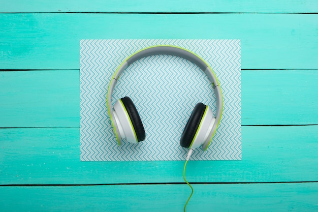 Wired stereo headphones on blue wooden boards with paper