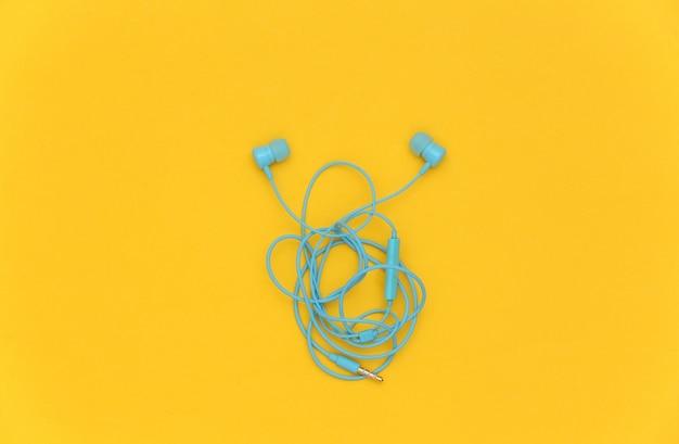 노란색 배경에 유선된 얽힌 헤드폰입니다. 평면도. 플랫 레이