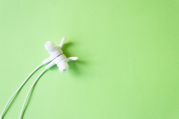 Wired white headphones on a green wall