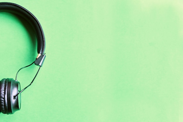 Wireless black headphones on colorful green background