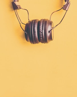 Wireless black headphones on colorful yellow background