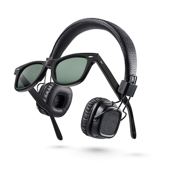 白い背景で隔離のワイヤレス黒オンイヤーヘッドフォンとプラスチックサングラス