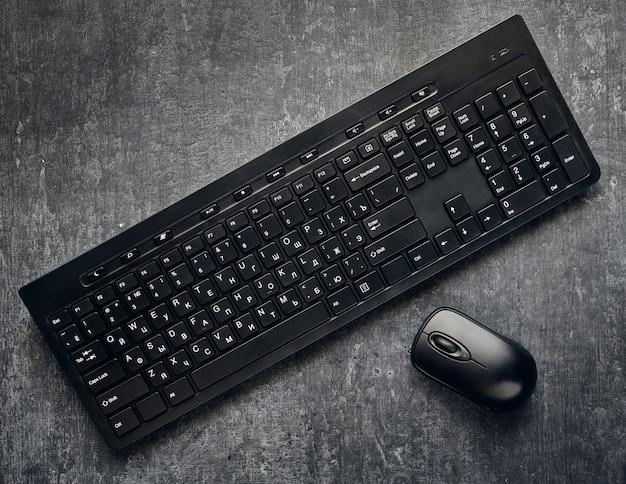 Беспроводная компьютерная клавиатура и мышь на сером фоне