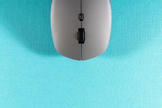Беспроводная компьютерная мышь на синем фоне.