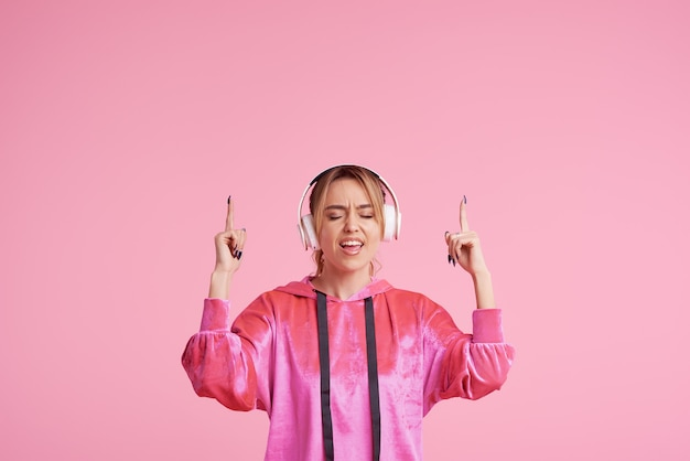 Беспроводное соединение. портрет молодой женщины позирует изолированные над розовый прослушивания веселой музыки с наушниками.