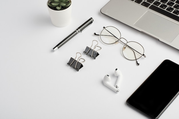 Wireless earphones, eyeglasses, pen, clips, mobile phone and laptop keypad on white desk that is workplace of employee