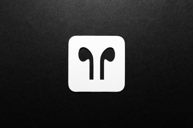 ワイヤレスイヤホン;黒い色の背景に白い紙に切り抜かれたイヤフォンのアイコン。