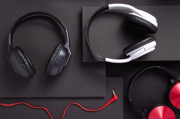 추상적인 검은색 종이 배경의 무선 이어폰 또는 헤드폰, 미니멀리즘 개념 스타일