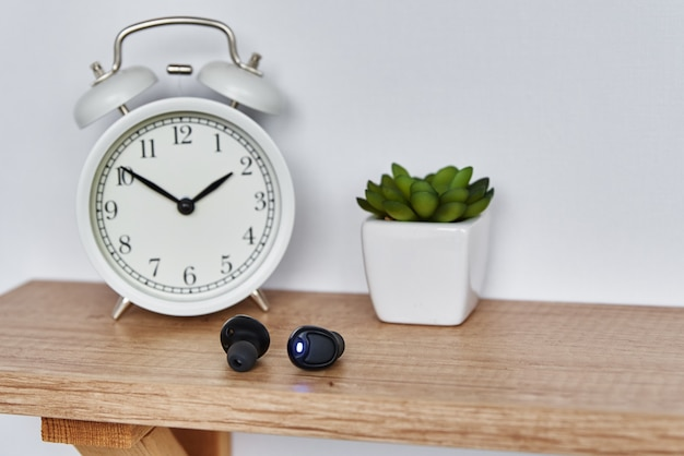 Wireless earphones on the shelf with alarm clock and house plant.