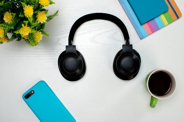 Беспроводные наушники смартфон и чашка кофе