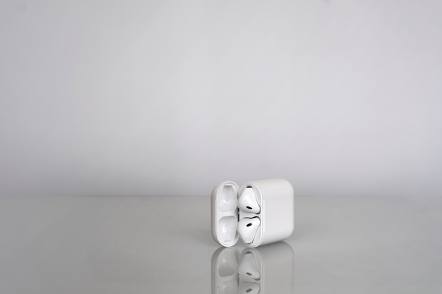 Wireless earphones with a charging box on grey background with reflection in the glass