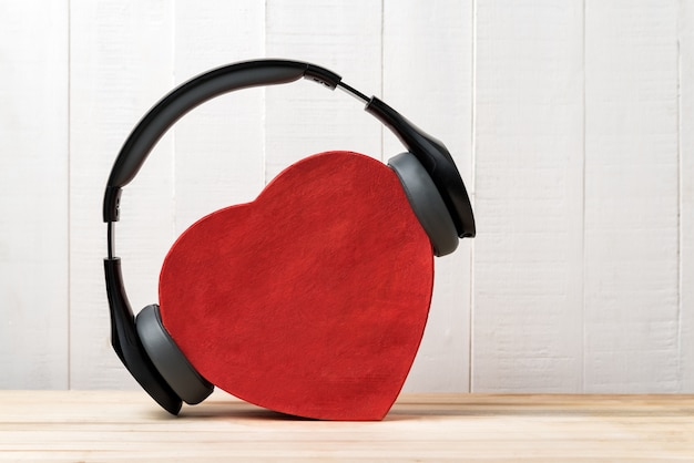 Wireless full-size headphones wearing a red heart-shaped box. love music concept. front view