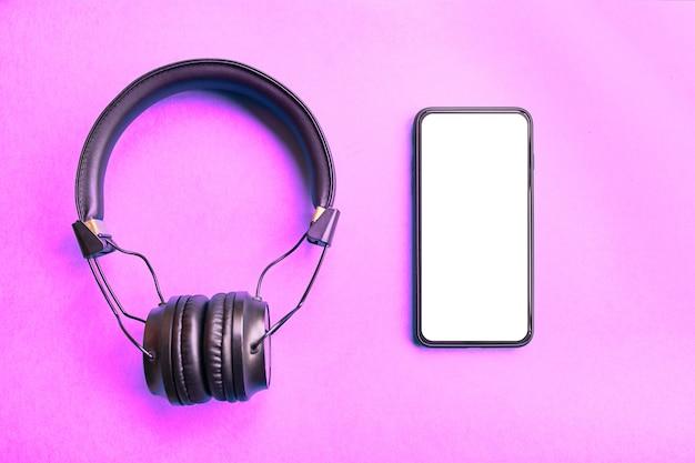 ワイヤレスヘッドフォンとカラフルな背景の上のフレームなしのスマートフォン