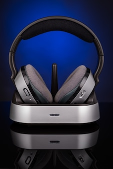 Wireless headphones on a blue background. with reflection.