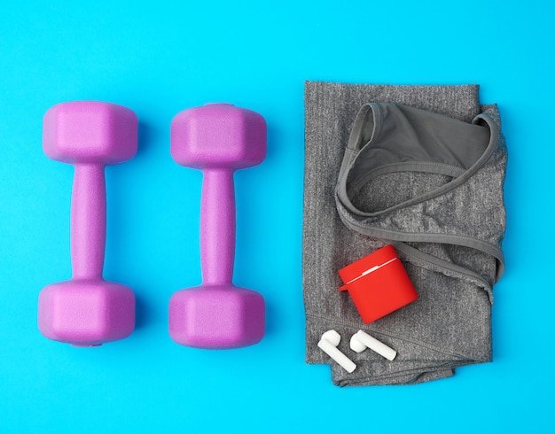 Wireless headphones and charging lie on a gray female sports jersey and a pair of plastic purple dumbbells