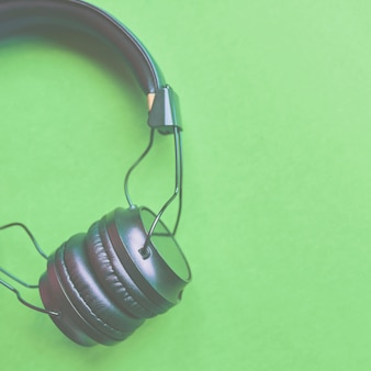Wireless headphones on colorful green background for music sound isolated. 1x1 crop