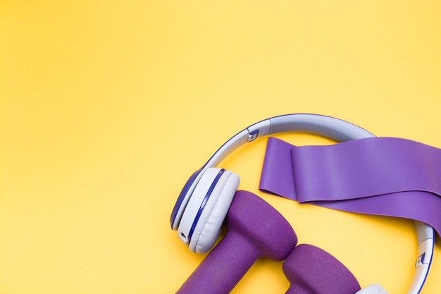 ワイヤレスヘッドフォン、ゴムバンド、黄色の背景に紫色のダンベル、コピースペース、上面図