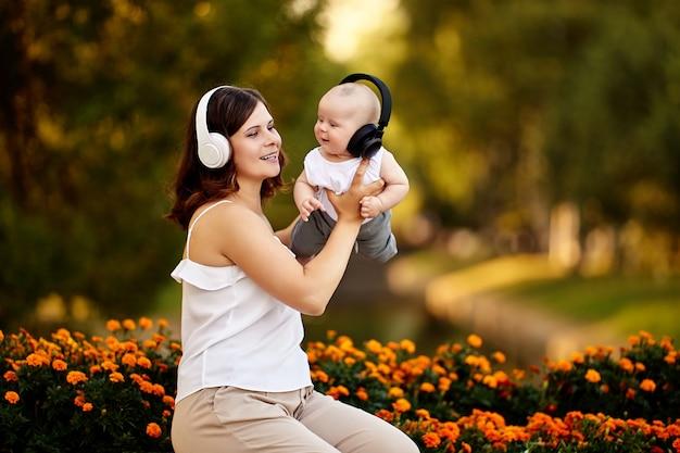 夏の夜の自然の中を散歩中の若い女性と彼女の赤ちゃんのためのワイヤレスヘッドフォン