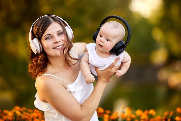幼児の男の子と彼の若い母親のワイヤレスヘッドフォン