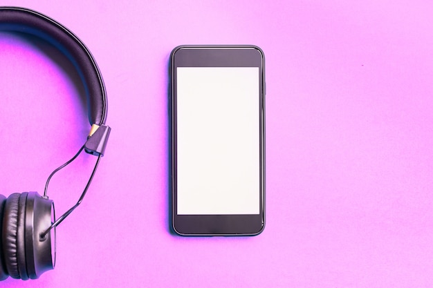 Wireless headphones and smartphone on colorful pink background