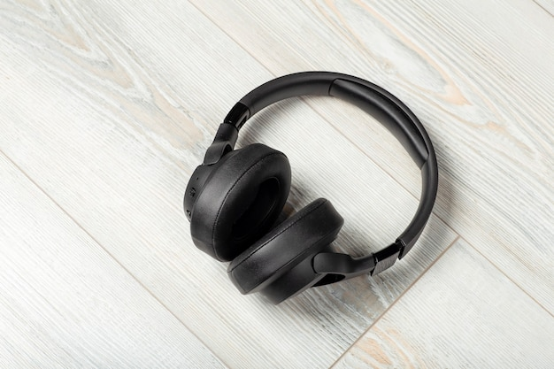Wireless headphones on a white wooden laminate floor background soundproofing music and sound in the...