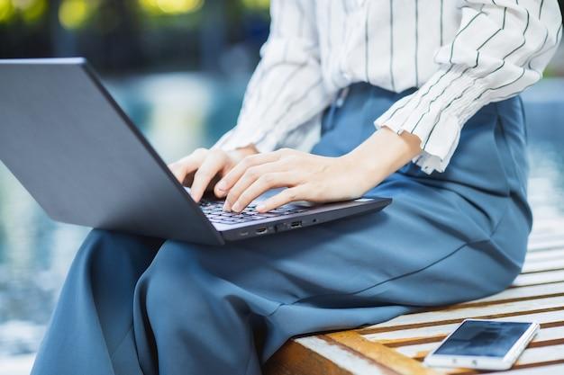 ビジネスコンセプトのワイヤレスインターネット技術、屋外でラップトップコンピューターとテキストチャットを入力して自宅から屋外で働くビジネスウーマン