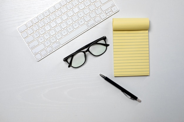 테이블에 안경 무선 키보드와 노란색 메모장