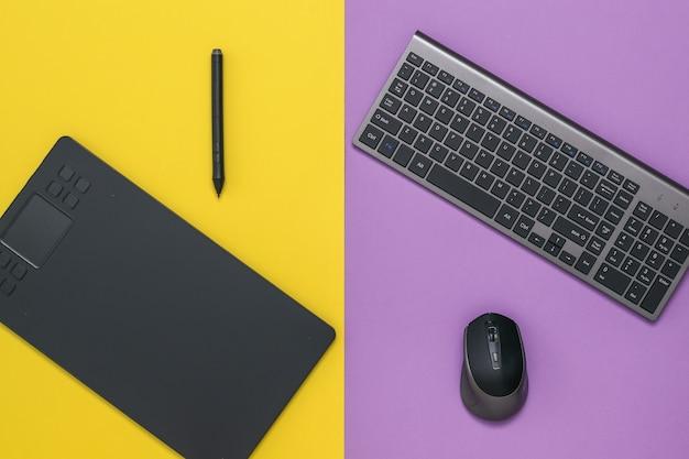 Беспроводная клавиатура, мышь и графический планшет на двухцветном столе. инструменты дизайнера.