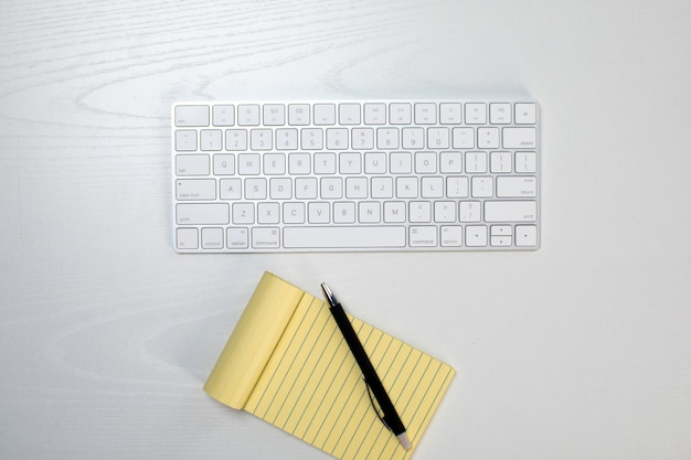 Wireless keyboard and yellow notepad on the table