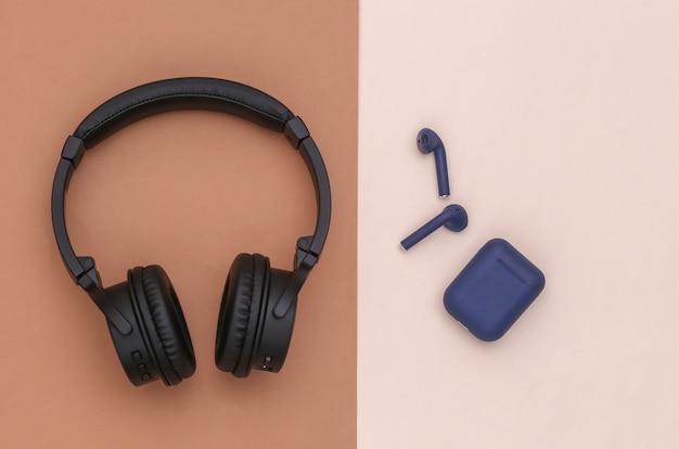 ブラウンベージュの背景に充電器ケース付きのワイヤレス大型ステレオヘッドフォンと小型イヤフォン。上面図