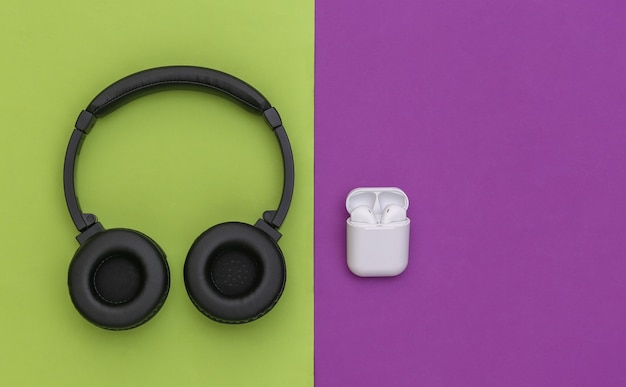 紫緑色の背景に充電器ケース付きのワイヤレス大型ステレオヘッドフォンと小型イヤフォン。上面図