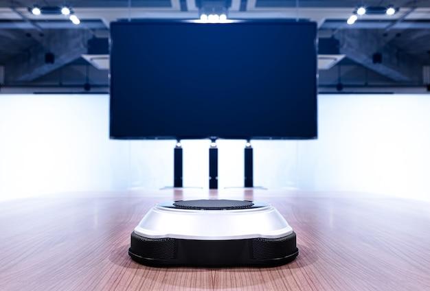 화상 회의 회의실의 빈 화면 tv가 있는 중간 회의 테이블에 휴대용 무선 마이크