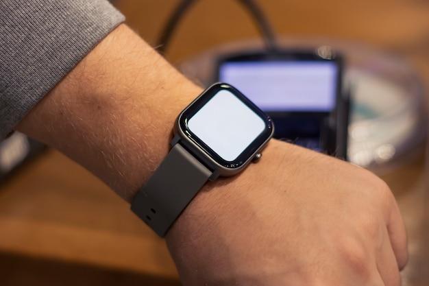 Беспроводная онлайн-оплата. макет умных часов с белым экраном на мужской руке на фоне терминала для платежей.