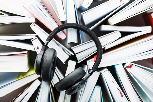 Wireless overhead black headphones lie on the books. the concept of learning through an audiobook. to listen to the book.