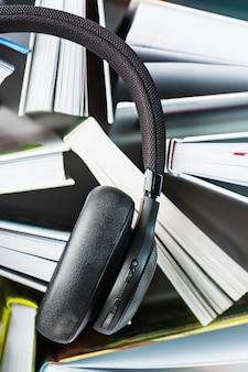 책 위에는 무선 오버 헤드 블랙 헤드폰이 있습니다. 오디오 북을 통한 학습의 개념. 책을 듣습니다.
