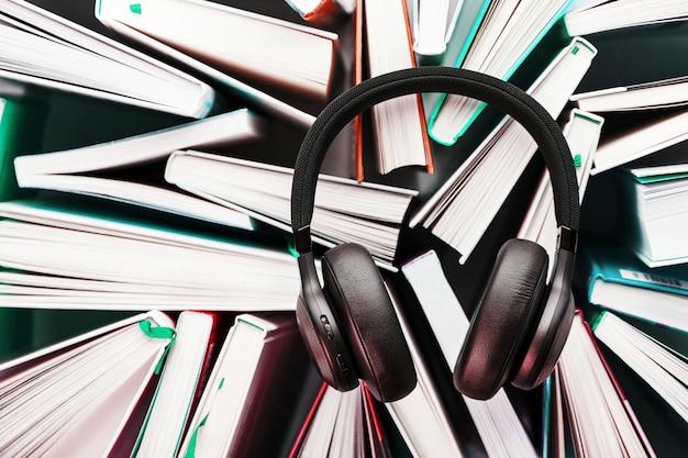 Беспроводные накладные черные наушники лежат на книгах