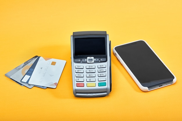 黄色の背景にクレジットカードまたはnfc決済、携帯電話、クレジットカード用のワイヤレス決済端末。広告用のコピースペース、パノラマ。