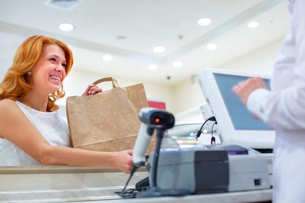 스마트 폰 및 nfc 기술을 사용한 무선 결제 확대. 가 게에서 스마트 폰으로 지불하는 여성 고객. 쇼핑을 닫습니다