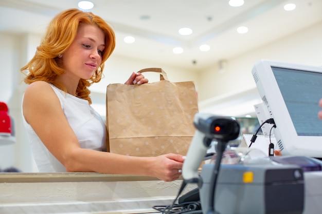 Беспроводная оплата с использованием смартфона и технологии nfc. закройте женский клиент оплачивая с умным телефоном в магазине. close up shopping