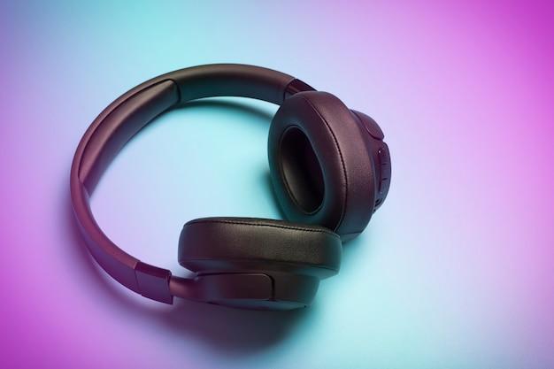무선 사운드 컬러 네온 배경에 오디오 헤드폰입니다. 음악 앱, 팟캐스트, 라디오 및 오디오북 개념 듣기. 고품질 사진